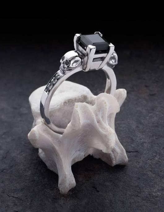 Thyone ist ein gothic Damenring mit Totenköpfen und schwarzen Diamanten. Eine stabile Fassung hält den viereckigen, quadratisch geschliffenen Edelstein in der Mitte. Seitlich unter den Totenköpfen ist der Ring mit je drei Diamanten besetzt. Gezeigt wird der Ring auf einem Knochen stehend.