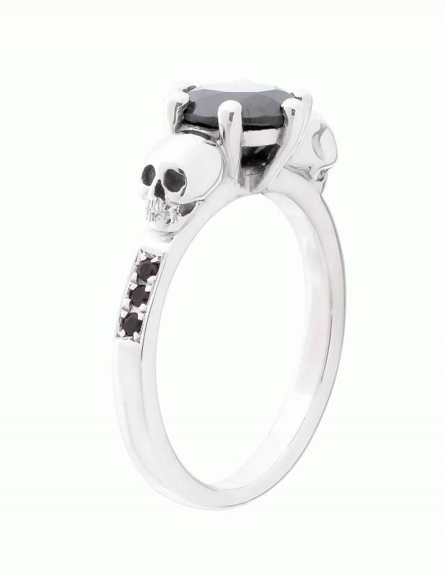 Thana ist ein mystischer Ring mit Totenköpfen und funkelnden Diamanten. Eine zarte Fassung hält den runden, facettierten Edelstein in der Mitte. An den Seiten ist der Ring mit je drei Diamanten besetzt. Ansicht von der Seite.