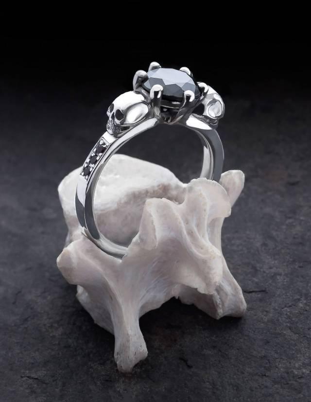 Thana ist ein mystischer Ring mit Totenköpfen und funkelnden Diamanten. Eine zarte Fassung hält den runden, facettierten Edelstein in der Mitte. An den Seiten ist der Ring mit je drei Diamanten besetzt. Gezeigt wird der Ring auf einem Knochen stehend.