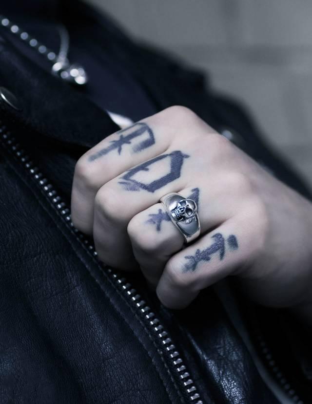 BEHEMOTH: Glatter Siegelring mit Totenkopf für Männer. Plastisch gearbeitet. Alle Vertiefungen sind von Hand geschwärzt. Der Ring wird an einer Hand gezeigt.