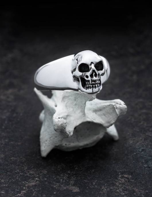 BEHEMOTH: Smooth signet ring with skull for men. Sculpturally worked. All depressions are blackened by hand. The ring lies on a bone in the picture.
