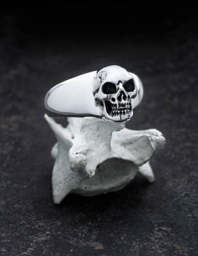 BEHEMOTH: Glatter Siegelring mit Totenkopf für Männer. Plastisch gearbeitet. Alle Vertiefungen sind von Hand geschwärzt. Der Ring liegt im Bild auf einem Knochen.