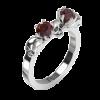 Hier zu sehen ist der Zusteckring für Wanda, der mit zwei runden, facettierten Edelsteinen und drei kleinen Totenköpfen besetzt ist. Der Ring auf dem Bild ist aus Silber mit einem Granat Edelstein gefertigt. Ansicht von schräg oben.