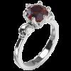 Wanda ist ein eleganter Totenkopfring mit einem großen, facettierten Edelstein. Die zwei detailliert gearbeiteten Totenköpfe halten die Fassung in ihrer Mitte. Der Ring auf dem Bild ist aus Silber mit einem Granat. Ansicht von schräg oben.