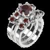 Wanda ist hier zu sehen im Dreierset mit zwei Zusteckringen, die jeweils mit vier kleinen, runden Edelsteinen und einem kleinen Totenkopf besetzt sind. Das Ringset auf dem Bild ist aus Silber mit einem Granat Edelsteinen. Ansicht von schräg oben.