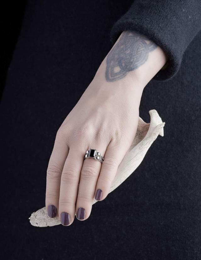 DAEMONA: ein großer gothic Ring mit schwarzen Diamanten. Ein besonderer Damenring mit Totenköpfen und einem schwarzen, rechteckigen Edelstein. Der Ring wird an einer Hand gezeigt.