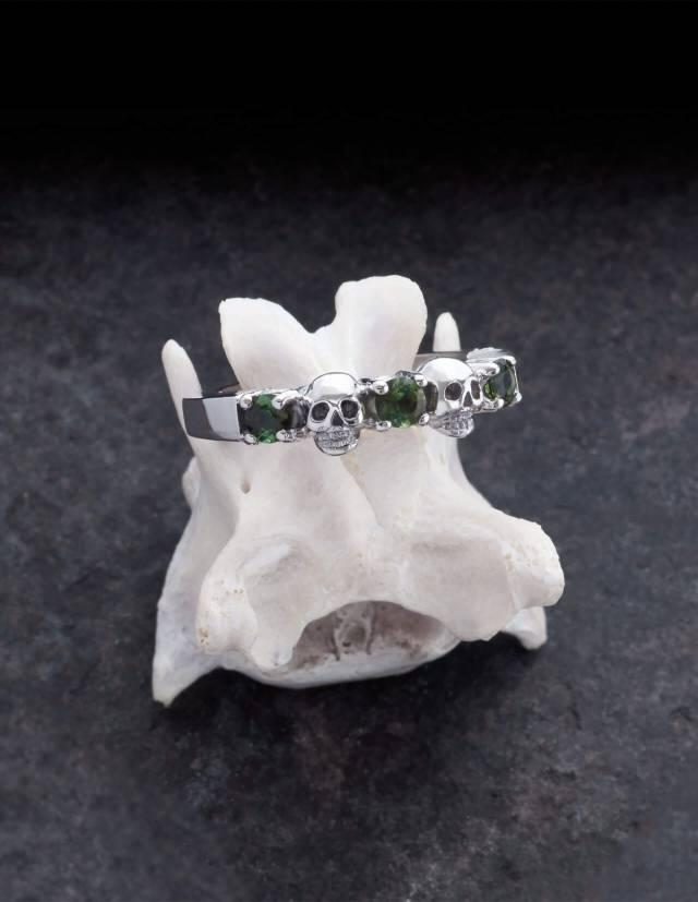 Echidna ist ein schmaler Ehering mit Totenköpfen und echten Edelsteinen deiner Wahl aus Silber. Zwei Totenköpfe und drei runde Edelsteine sind abwechselnd auf einem glatten Band angeordnet. Der Ring liegt auf einem Knochen.