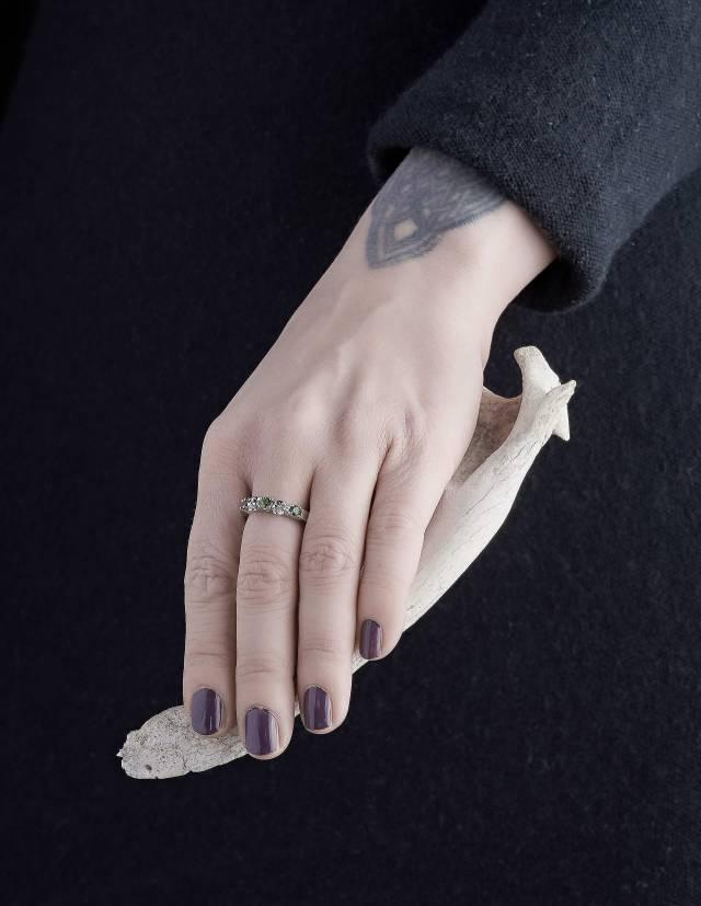 Echidna ist ein schmaler Ehering mit Totenköpfen und echten Edelsteinen deiner Wahl aus Silber. Zwei Totenköpfe und drei runde Edelsteine sind abwechselnd auf einem glatten Band angeordnet. Gezeigt an einer Hand.