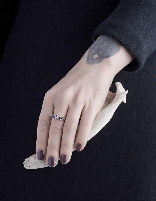 Helice ist ein prachtvoller Ehering mit einem Totenkopf umgeben von vier runden Edelsteinen. Der Ring ist aus Silber gefertigt in der Goldschmiede Kipkalinka. Gezeigt an einer Hand.