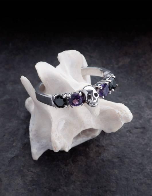 Helice ist ein prachtvoller Ehering mit einem Totenkopf umgeben von vier runden Edelsteinen. Der Ring ist aus Silber gefertigt in der Goldschmiede Kipkalinka. Der Ring liegt auf einem Knochen.