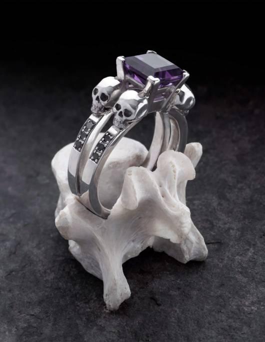 Lethe ist ein massiver Totenkopf Damenring mit schwarzen Diamanten und einem eckigen Amethyst Edelstein aus der Goldschmiede Kipkalinka. Gezeigt auf einem Knochen.