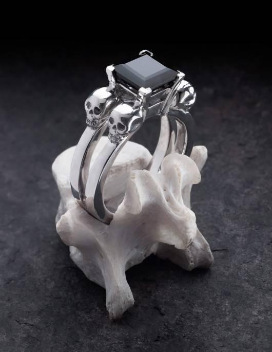 Lethe ist ein Totenkopfring für Frauen aus Silber. In der Mitte sitzt ein schwarzer, eckiger Edelstein. Gezeigt auf einem Knochen.