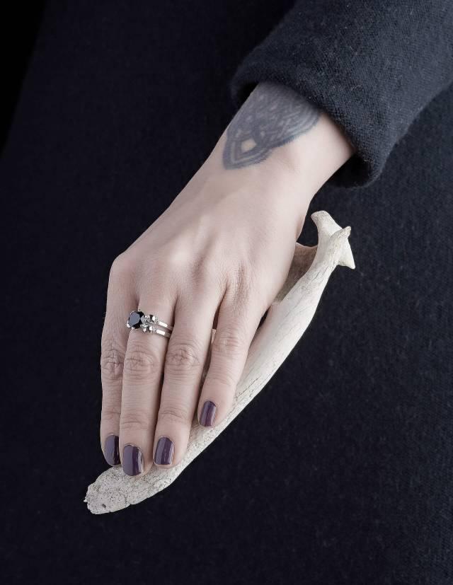 Lilith ist ein edler Totenkopfring für gothic Frauen. Der schlichte Ring ist aus Silber gefertigt und trägt zwischen vier kleinen Totenköpfen einen schwarzen Edelstein in der Mitte. Gezeigt an einer Hand.