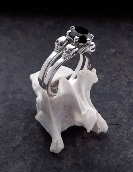 Lilith ist ein edler Totenkopfring für gothic Frauen. Der schlichte Ring ist aus Silber gefertigt und trägt zwischen vier kleinen Totenköpfen einen schwarzen Edelstein in der Mitte. Gezeigt auf einem Knochen stehend.