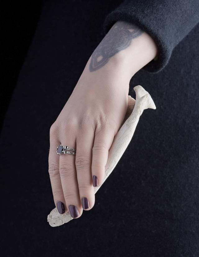 Lilith ist ein eleganter Totenkopfring mit schwarzen Diamanten und einem runden, schwarzen Edelstein. Der Ring ist aus Silber und der perfekte gothic Verlobungsring. Gezeigt an einer Hand.