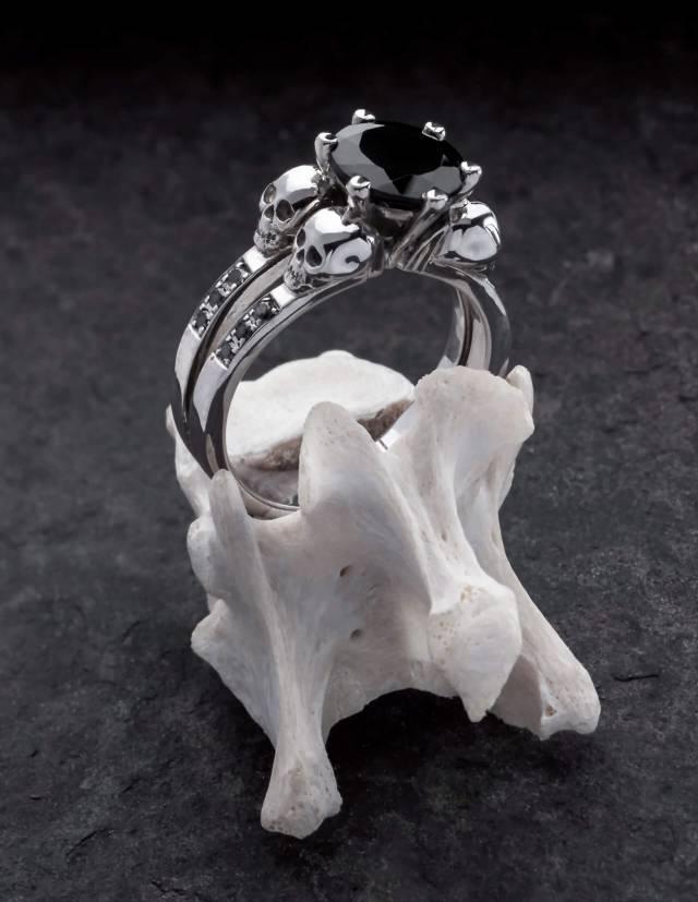 Lilith ist ein eleganter Totenkopfring mit schwarzen Diamanten und einem runden, schwarzen Edelstein. Der Ring ist aus Silber und der perfekte gothic Verlobungsring. Der Ring ist auf einem Knochen drapiert.