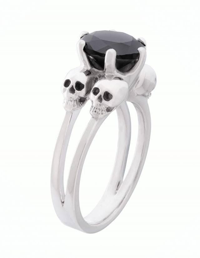 Varla ist ein Verlobungsring mit kleinen Totenköpfen aus Silber. Zwischen den vier Totenschädeln sitzt ein großer, runder Edelstein. Seitenansicht.