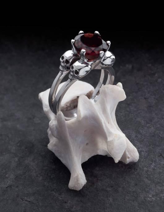 Varla ist ein Verlobungsring mit kleinen Totenköpfen aus Silber. Zwischen den vier Totenschädeln sitzt ein großer, runder Edelstein. Der Ring ist auf einem Knochen drapiert.