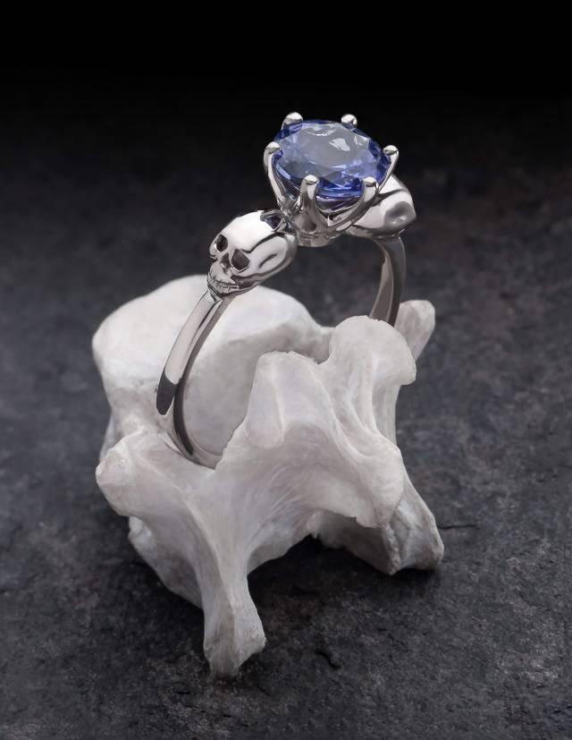 Wanda ist ein eleganter Totenkopfring mit einem großen, facettierten Edelstein. Die zwei detailliert gearbeiteten Totenköpfe halten die Fassung in ihrer MItte. Der Ring auf dem Bild ist aus Weißgold mit einem Tansanit und wird auf einem Knochen präsentiert.