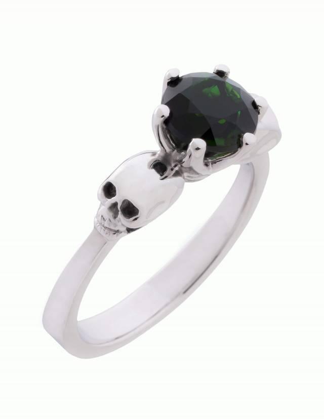 Wandika ist ein zarter Totenkopfring aus Silber für Damen. Er trägt einen kleinen schwarzen Edelstein in einer zarten Fassung. Ansicht von schräg oben.