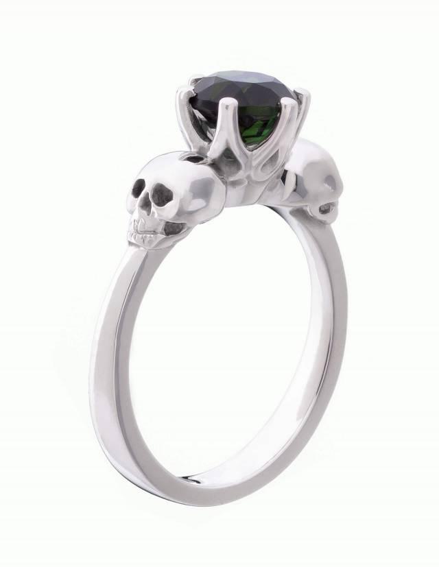 Wandika ist ein zarter Totenkopfring aus Silber für Damen. Er trägt einen kleinen schwarzen Edelstein in einer zarten Fassung. Seitenansicht.