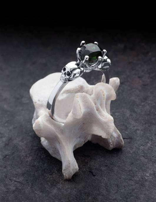 Wandika ist ein zarter Totenkopfring aus Silber für Damen. Er trägt einen kleinen schwarzen Edelstein in einer zarten Fassung. Gezeigt auf einem Knochen.