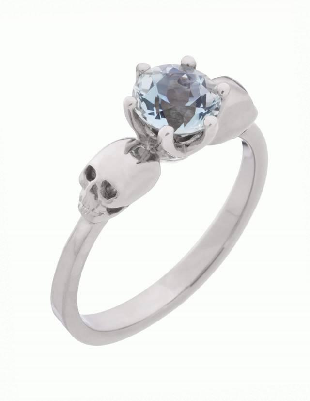 WANDIKA ist ein zierlicher Weißgold Ring mit Totenköpfen. Er trägt einen hellblauen Aquamarin Edelstein in seiner Mitte. Ansicht von oben.