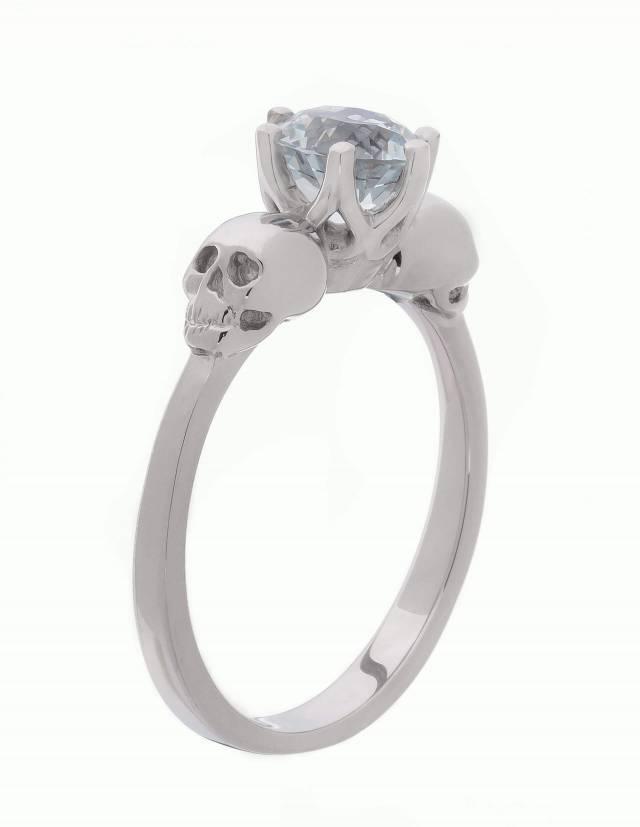 WANDIKA ist ein zierlicher Weißgold Ring mit Totenköpfen. Er trägt einen hellblauen Aquamarin Edelstein in seiner Mitte. Seitenansicht.