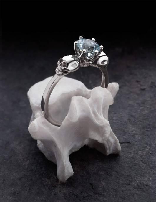 WANDIKA ist ein zierlicher Weißgold Ring mit Totenköpfen. Er trägt einen hellblauen Aquamarin Edelstein in seiner Mitte. Gezeigt auf einem Knochen.