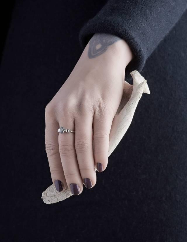 WANDIKA ist ein zierlicher Weißgold Ring mit Totenköpfen. Er trägt einen hellblauen Aquamarin Edelstein in seiner Mitte. Gezeigt an einer Hand.
