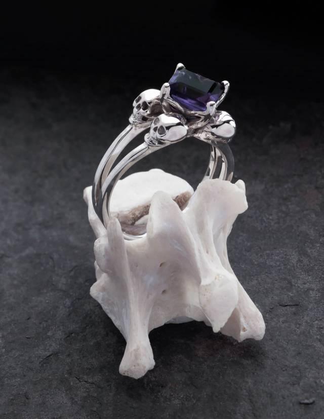 Zorya ist ein Totenkopfring aus Silber mit einem eckigen Edelstein für Frauen. Der Amethyst sitzt mittig zwischen vier kleinen Totenköpfen. Gezeigt auf einem Knochen.