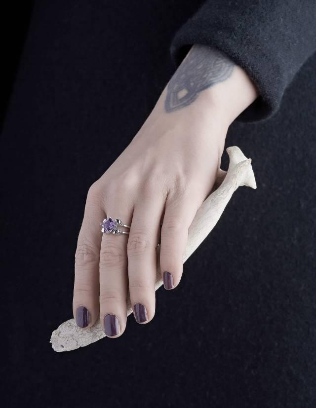 Zorya ist ein Totenkopfring aus Silber mit einem eckigen Edelstein für Frauen. Der Amethyst sitzt mittig zwischen vier kleinen Totenköpfen. Gezeigt an einer Hand.