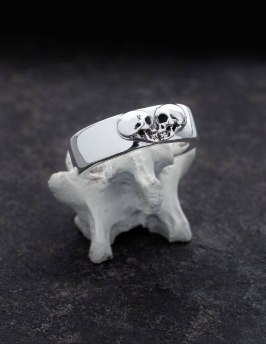 Kissing Skulls is a solid gothic silver ring. Two skulls in profile are arranged in the shape of a heart. The shape of the ring is wide and slightly flat domed with rounded edges. The ring is shown on a bone.