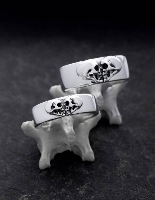 Alt-Tag (Bildtitel als Fließtext): Kissing Skulls sind ein Paar schwerer Trauringe aus 925er Silber für echte Rocker. Die zwei Totenköpfe im Profil bilden eine Herzform. Die Eheringe sind breit und flach gewölbt. Die Ringe sind auf Knochen zu sehen.