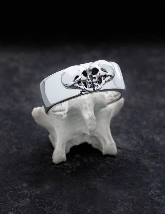 Kissing Skulls ist ein schwerer gothic Ehering. Zwei Totenköpfe im Profil sind in Form eines Herzens angeordnet. Die Form des Ringes ist breit und leicht flach gewölbt mit abgerundeten Kanten. Der Ring ist in diesem Bild auf einem Knochen drapiert.