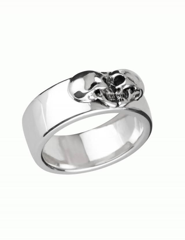 Kissing Skulls ist ein schwerer gothic Ehering. Zwei Totenköpfe im Profil sind in Form eines Herzens angeordnet. Die Form des Ringes ist breit und leicht flach gewölbt mit abgerundeten Kanten. Draufsicht seitlich.