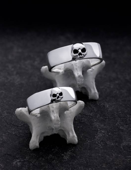 Amun and Amunet are a pair of simple wedding rings with detailed skulls without lower jaws. The ladies' ring is slightly smaller and narrower than the men's ring. Both wedding rings have a flat shape that is very slightly curved on the inside and outside. They are presented standing one behind the other on bone.