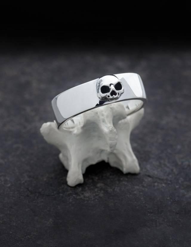Amun ist ein schlichter Bandring aus Silber mit detailliertem Totenkopf ohne Unterkiefer. Der Ring hat eine flache, innen und außen ganz leicht gewölbte Form. Präsentiert wird er auf einem Knochen stehend.