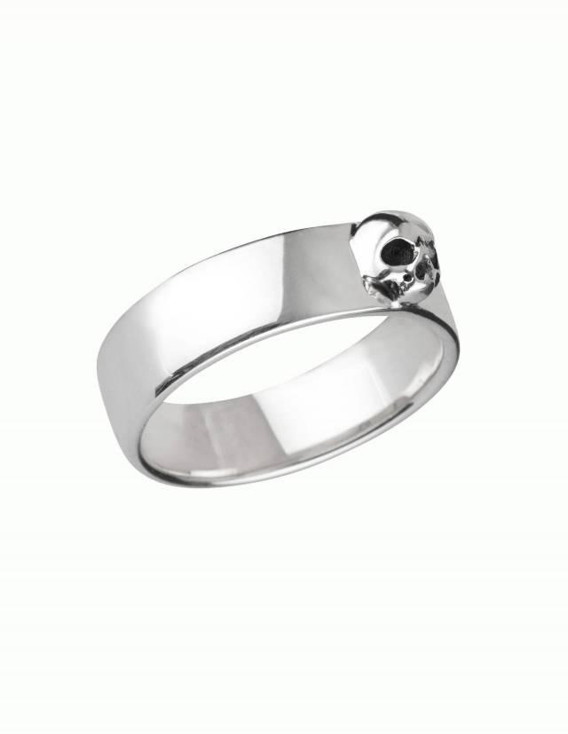 Amunet ist ein dezenter Bandring aus Silber mit einem plastisch gearbeiteten Totenkopf ohne Unterkiefer. Der Ring hat eine flache, innen und außen ganz leicht gewölbte Form, die Kanten sind abgerundet. Seitenansicht.