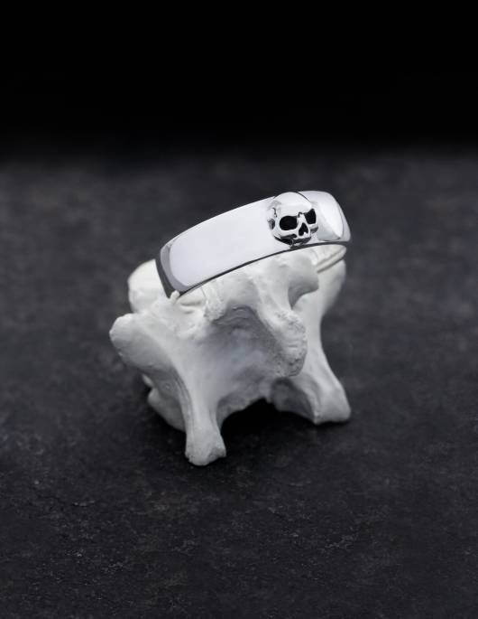Amunet is a discreet band ring made of silver with a sculpted skull without a lower jaw. The ring has a flat shape, slightly curved on the inside and outside, the edges are rounded. It is presented standing on a bone.