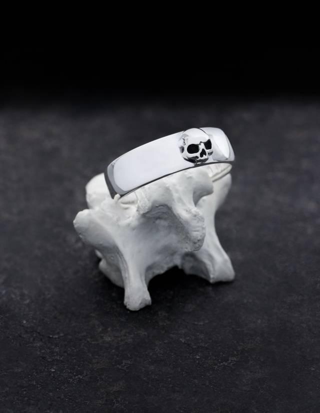 Amunet ist ein dezenter Bandring aus Silber mit einem plastisch gearbeiteten Totenkopf ohne Unterkiefer. Der Ring hat eine flache, innen und außen ganz leicht gewölbte Form, die Kanten sind abgerundet. Präsentiert wird er auf einem Knochen stehend.