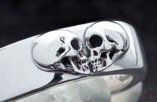 """Das Bild zeigt eine Nahaufname eines Ringes aus Silber mit zwei Totenköpfen, die sich gegenüberstehen, als ob sie sich küssen. Zusammen bilden sie die Form eines Herzens. Ein Klick auf das Bild führt zur Kategorie """"Gothic Eheringe"""" im Shop, wo es außergewöhnliche Eheringe zu kaufen gibt."""