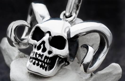 """Das Bild zeigt einen silbernen Anhänger in Form eines Totenschädels mit Hörnern in Großaufnahme. Ein Klick auf das Bild führt zur Kategorie """"Totenkopf-Ketten"""" im Shop, wo es Halsschmuck und Kettenanhänger mit Totenköpfen zu kaufen gibt."""