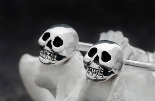"""Das Bild zeigt zwei silberne Ohrstecker mit Totenköpfen in Nahaufname. Ein Klick auf das Bild führt zur Kategorie """"Totenkopf-Ketten"""" im Shop, wo es Ohrringe und Ohrstecker mit Totenköpfen zu kaufen gibt."""