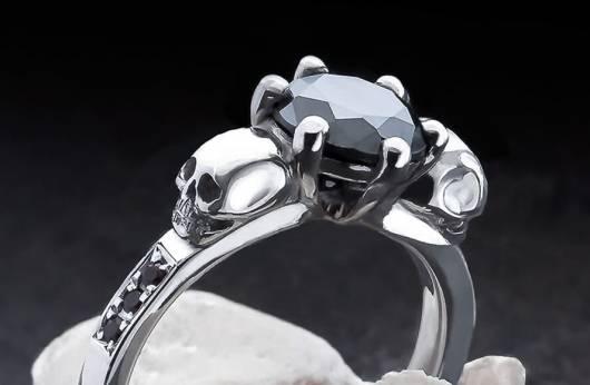 """Auf dem Bild ist ein zarter Ring mit kleinen Totenköpfen und geschliffenen Edelsteinen zu sehen. Der große Stein in der Mitte ist ein schwarzer Edelstein, die kleinen an den Seiten schwarze Diamanten. Das Bild führt zur Kategorie """"Totenkopf-Ringe mit Edelsteinen"""" im Shop von Kipkalinka."""