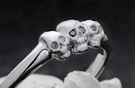 """Auf dem Bild ist ein zarter Ring aus Platin mit drei kleinen Totenköpfen zu sehen. Der mittlere von ihnen hat geschliffene, schwarze Diamanten als Augen eingesetzt. Ein Klick auf das Bild führt zur Kategorie """"Zarte Totenkopfringe"""" im Shop von Kipkalinka."""
